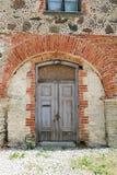 Puerta de madera medieval vieja en una pared de piedra fotos de archivo libres de regalías