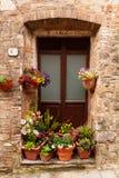 Puerta de madera rodeada por las flores coloridas en Toscana, Italia imagenes de archivo
