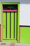 Puerta de madera rosada verde de un frente colonial de la casa Foto de archivo