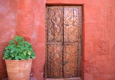 Puerta de madera tallada vieja en la pared áspera anaranjada del color rojo con los plantadores grandes de una terracota en Santa foto de archivo libre de regalías