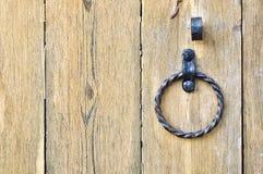 Puerta de madera texturizada vieja con el tirador de puerta envejecido del metal bajo la forma de anillo fotografía de archivo
