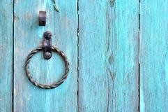 Puerta de madera texturizada vieja de la turquesa con el tirador de puerta envejecido del metal bajo la forma de anillo Fotografía de archivo