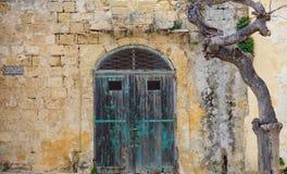 Puerta de madera vieja cerrada en una pared amarilla de la piedra caliza Mdina, Malta imagen de archivo libre de regalías