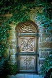 Puerta de madera vieja con el modelo tallado en un jardín misterioso Fotos de archivo