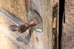 Puerta de madera vieja con la manija oxidada vieja Foto de archivo libre de regalías
