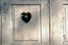 Puerta de madera vieja con un corazón romántico tallado Foto de archivo libre de regalías