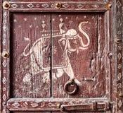 Puerta de madera vieja con una imagen de un elefante. Fragmento. Imagen de archivo