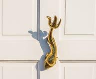 Puerta de madera vieja a contener con un golpeador de cobre amarillo en la forma de a Imágenes de archivo libres de regalías