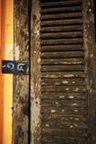 Puerta de madera vieja en la pared anaranjada imagenes de archivo
