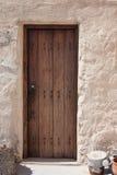 Puerta de madera vieja en la pared de piedra Foto de archivo libre de regalías