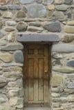 Puerta de madera vieja en la pared de piedra Imagenes de archivo