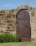 Puerta de madera vieja en la pared de piedra del jardín Imagen de archivo