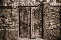 Puerta de madera vieja en una pared de ladrillo foto de archivo libre de regalías