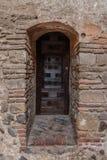 Puerta de madera vieja en una pared de ladrillo fotos de archivo libres de regalías