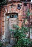 Puerta de madera vieja de la casa del ladrillo rojo fotografía de archivo