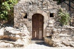 Puerta de madera vieja a un sótano de piedra en una casa griega Fotos de archivo libres de regalías