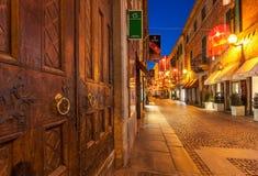 Puerta de madera y calle estrecha de Alba en la noche Imagen de archivo