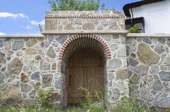 Puerta de madera y pared de piedra Imagen de archivo libre de regalías