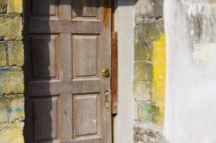 Puerta de madera y pared de ladrillo amarilla fotos de archivo libres de regalías