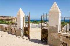 Puerta del metal que desmenuza de la pared de piedra colonial que pasa por alto el océano hermoso en Angola Foto de archivo
