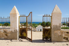 Puerta del metal que desmenuza de la pared de piedra colonial que pasa por alto el océano hermoso en Angola imágenes de archivo libres de regalías