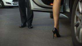 Puerta del vehículo de la abertura del caballero, mujer de ayuda que consigue en el coche, cierre para arriba de piernas almacen de video