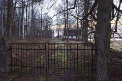 Puerta delante de poca cabaña blanca en bosque misterioso Fotografía de archivo