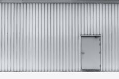 Puerta en el almacén de aluminio de la fábrica de la pared imagen de archivo libre de regalías