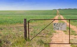 Puerta en el extremo de la pista a través de la granja Foto de archivo libre de regalías
