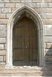 puerta gótica vieja en una pared de piedra gruesa Fotografía de archivo libre de regalías