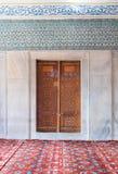 Puerta grabada envejecida de madera, pared de mármol y baldosas cerámicas con los modelos decorativos azules florales, Sultan Ahm Fotos de archivo libres de regalías