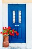 Puerta griega de la casa adentro con las flores del geranio Imagen de archivo