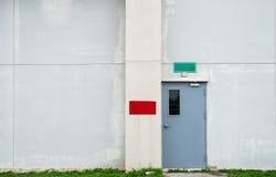 Puerta gris cerrada con el cuadro de texto verde y rojo en el muro de cemento blanco Foto de archivo