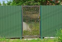 Puerta gris cerrada del metal con un modelo forjado y una cerca verde afuera fotos de archivo libres de regalías