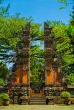 Puerta indonesia de Bali con estilo del ladrillo rojo y árbol verde en el fondo - foto Indonesia foto de archivo libre de regalías