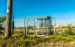 Puerta industrial del metal con el torniquete, porción abandonada en backgroun Fotografía de archivo libre de regalías