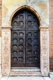Puerta medieval tallada adornada con los remaches metálicos Foto de archivo libre de regalías