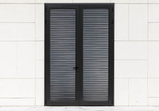 Puerta negra en la pared blanca con el embaldosado Fotografía de archivo libre de regalías