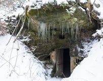 Puerta oscura abierta del sótano en cueva de la roca de la piedra arenisca con los carámbanos del musgo y de los liquenes y de la foto de archivo libre de regalías