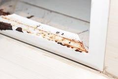Puerta oxidada del metal de la portilla sanitaria con la peladura de la pintura como resultado de humedad en el cuarto de baño, f imagenes de archivo