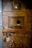 Puerta oxidada vieja de la prisión con una cerradura Fotos de archivo libres de regalías