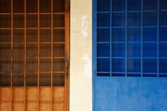 Puerta-parrilla azul y anaranjada en la calle imagenes de archivo