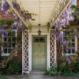 Puerta preciosa rodeada por las plantas y las flores hermosas imagen de archivo