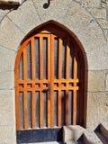 Puerta principal de madera con el arco y vidrio en un edificio de piedra viejo Foto de archivo