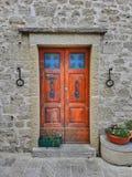 Puerta principal de madera en una pared de piedra vieja Fotografía de archivo