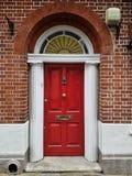 Puerta principal de madera roja con el arco y pilares en un edificio de ladrillo Fotos de archivo libres de regalías