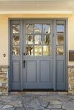 Puerta principal gris a un hogar con el pórtico de la pizarra Fotos de archivo libres de regalías