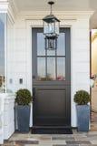 Puerta principal negra enmarcada por las plantas Foto de archivo
