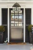 Puerta principal negra a un domicilio familiar con el pórtico Imagen de archivo libre de regalías