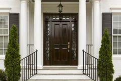 Puerta principal oscura con las columnas blancas fotografía de archivo